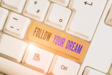 Text sign showing Follow Your Dream. Business photo text Keep track on your goals Live the life you want to be White pc keyboard with empty note paper above white background key copy space