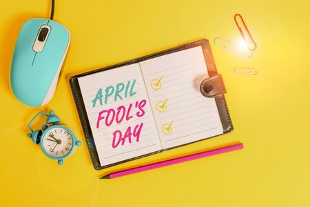 Word writing text April Fool S Day. Business photo showcasing Practical jokes humor pranks Celebration funny foolish Locked diary sheets clips marker mouse alarm clock colored background Reklamní fotografie