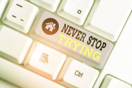 Conceptual hand writing showing Never Stop Trying. Concept meaning Do not give up Continue to Try Again Keep on Doing White pc keyboard with note paper above the white background