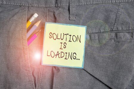 Text sign showing Solution Is Loading. Business photo showcasing thinking of way to solve big problems Diagnoses Writing equipment and green note paper inside pocket of man work trousers Stock fotó