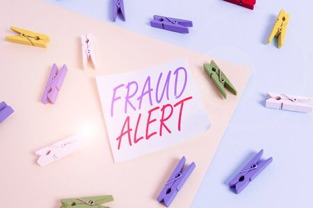 Text sign showing Fraud Alert. Business photo showcasing security alert placed on credit card account for stolen identity Colored clothespin paper empty reminder yellow blue floor background office