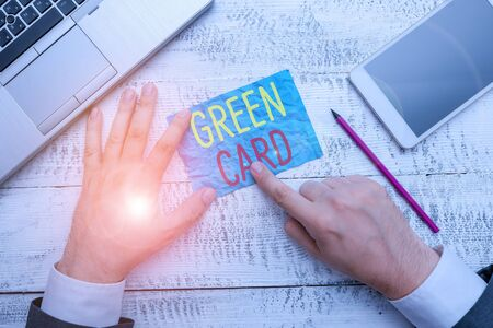 Conceptual hand writing showing Green Card. Concept meaning permit allowing a foreign national to live peranalysisently in the US Hand hold note paper near writing equipment and smartphone