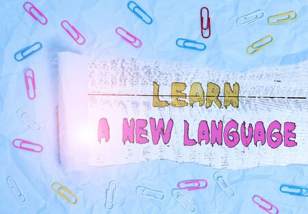 Writing note showing Learn A New Language. Business concept for Study Words other than the Native Mother Tongue Paper clip and torn cardboard on wood classic table backdrop