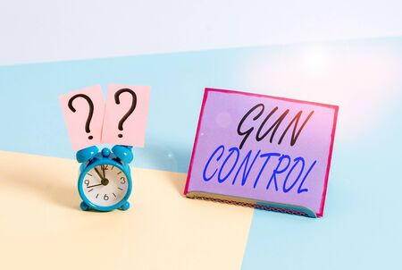 Word writing text Gun Control. Business photo showcasing legal measure intended to restrict the possession of guns Mini size alarm clock beside a Paper sheet placed tilted on pastel backdrop