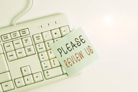 Writing note showing Please Review Us. Business concept for Give a feedback Opinion Comments Quality of service White pc keyboard with empty note paper above white background Reklamní fotografie
