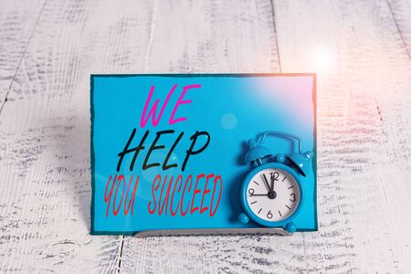 Conceptual hand writing showing We Help You Succeed. Concept meaning Aided Supported Funded someone to reach his dreams Alarm clock tilted above buffer wire in front of notepaper