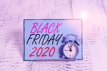 Conceptual hand writing showing Black Friday 2020. Concept meaning day following Thanksgiving Discounts Shopping day Alarm clock tilted above buffer wire in front of notepaper