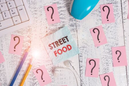 Writing note showing Street Food. Business concept for cooked food sold by vendors in a street or other public location Writing tools and scribbled paper on top of the wooden table