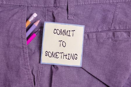 Text sign showing Commit To Something. Business photo showcasing To Live a Life of Purpose with Pride Honor a Promise Writing equipment and green note paper inside pocket of man work trousers