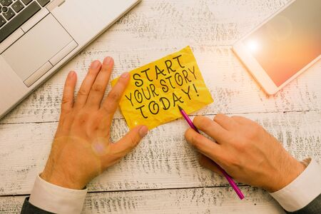 Text sign showing Start Your Story Today. Business photo text work hard on yourself and begin from this moment Hand hold note paper near writing equipment and modern smartphone device