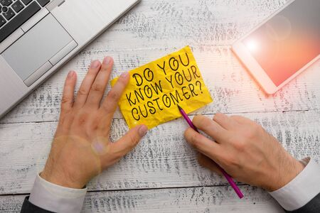 Text sign showing Do You Know Your Customer Question. Business photo text service identify clients with relevant information Hand hold note paper near writing equipment and modern smartphone device