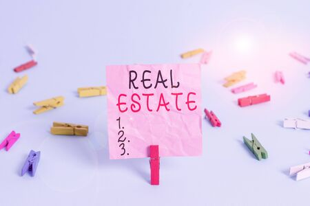 Handwriting text Real Estate. Conceptual photo the property consisting of land and the buildings on it Colored clothespin rectangle square shaped paper light blue background
