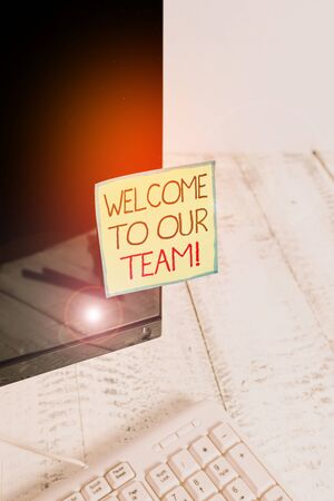 Handwriting text Welcome To Our Team. Conceptual photo introducing another demonstrating to your team mates Notation paper taped to black computer monitor screen near white keyboard 写真素材