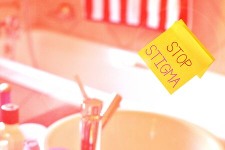 Word writing text Stop Stigma. Business photo showcasing end the feeling of disapproval that most showing in society have Piece of square yellow sheet use to give notation stick to washroom mirror