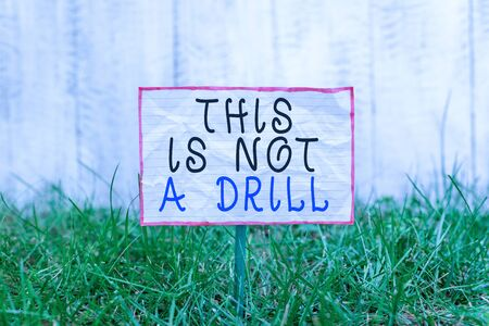 Text sign showing This Is Not A Drill. Business photo text practice actions Making test false majors Training Crumpled paper attached to a stick and placed in the green grassy land