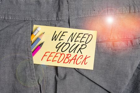 Writing note showing We Need Your Feedback. Business concept for criticism given to say can be done improvement Writing equipment and yellow note paper inside pocket of man trousers