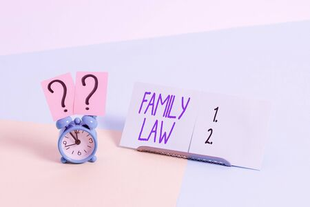 Writing note showing Family Law. Business concept for the branch of law that deals with matters relating to the family Alarm clock beside a Paper sheet placed on pastel backdrop