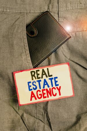 Conceptual hand writing showing Real Estate Agency. Concept meaning Business Entity Arrange Sell Rent Lease Manage Properties Small wallet inside trouser front pocket near notation paper