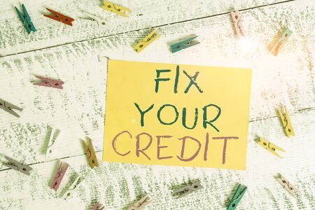 Conceptual hand writing showing Fix Your Credit. Concept meaning Keep balances low on credit cards and other credit Colored clothespin rectangle shaped paper blue background Stockfoto