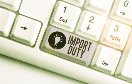 Writing note showing Import Duty. Business concept for tax imposed by a government on goods from other countries White pc keyboard with note paper above the white background