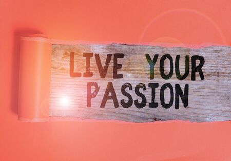 Word writing text Live Your Passion. Business photo showcasing Doing something you love that you do not consider a job Cardboard which is torn in the middle placed above a wooden classic table