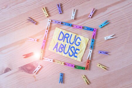 Writing note showing Drug Abuse. Business concept for the habitual taking of addictive or illegal chemical substances Colored clothespin papers empty reminder wooden floor background office