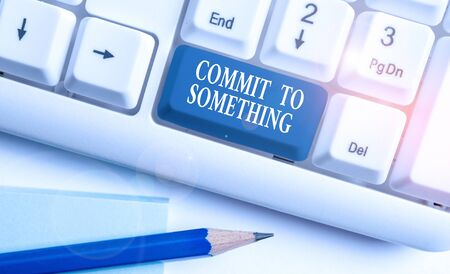 Conceptual hand writing showing Commit To Something. Concept meaning To Live a Life of Purpose with Pride Honor a Promise White pc keyboard with note paper above the white background