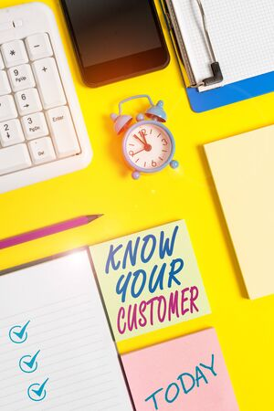 Writing note showing Know Your Customer. Business concept for Marketing creating a poll improve product or brand White paper with copy space with paper clips clock and pc keyboard