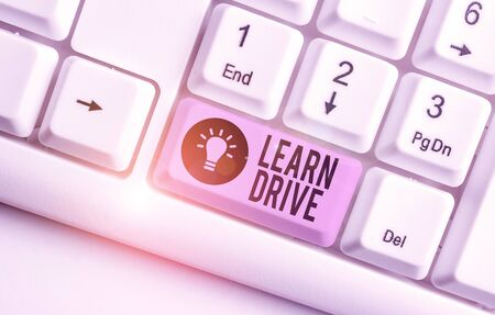 Writing note showing Learn Drive. Business concept for to gain the knowledge or skill in driving a motor vehicle White pc keyboard with note paper above the white background