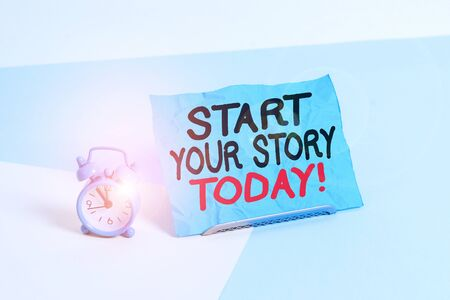 Writing note showing Start Your Story Today. Business concept for work hard on yourself and begin from this moment Alarm clock beside a Paper sheet placed on pastel backdrop