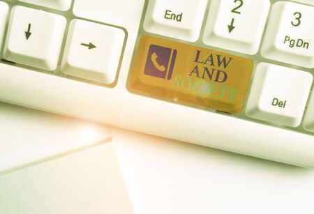 Text sign showing Law And Society. Business photo showcasing Address the mutual relationship between law and society White pc keyboard with empty note paper above white background key copy space Фото со стока