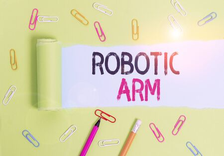 Word writing text Robotic Arm. Business photo showcasing programmable mechanical arm with similar function of a huanalysis arm Stationary and torn cardboard placed above a plain pastel table backdrop