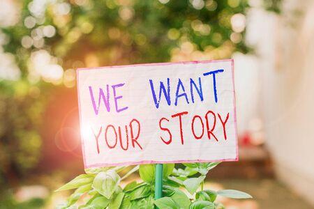 Escritura a mano conceptual mostrando que queremos tu historia. Concepto Significado Díganos algo un vistazo acerca de su historia de vida Papel normal adjunto a pegar y colocado en la tierra cubierta de hierba Foto de archivo