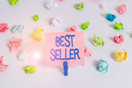 Writing note showing Best Seller. Business concept for new book or other product that has sold a great number of copies Colored crumpled paper empty reminder white floor clothespin