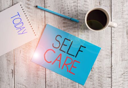 Writing note showing Self Care. Business concept for the practice of taking action to improve one s is own health Stationary placed next to a cup of black coffee above the wooden table Stock fotó