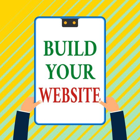Writing note showing Build Your Website. Business concept for Setting up an ecommerce system to market a business White rectangle clipboard with blue frame has two holes holds by hands