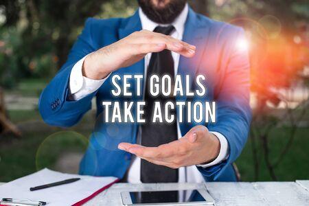 Conceptueel handschrift met gestelde doelen actie ondernemen. Concept betekent handelen op een specifieke en duidelijk vastgelegde plannen Man voor tafel. Mobiele telefoon en notities op tafel