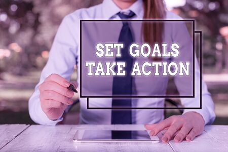 Text sign showing Set Goals Take Action. Business photo showcasing Act on a specific and clearly laid out plans Female business person sitting by table and holding mobile phone