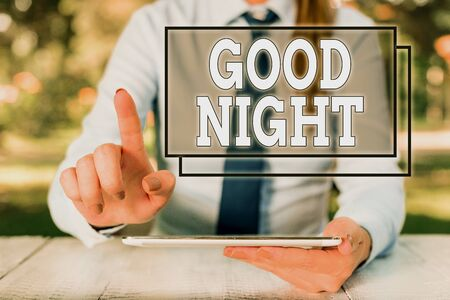 Text sign showing Good Night. Business photo text expressing good wishes on parting at night or before going to bed Female business person sitting by table and holding mobile phone