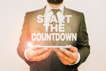 Text sign showing Start The Countdown. Business photo text Sequence of Backward Counting to Set the Timer Male human wear formal work suit hold smart hi tech smartphone use hands Stock Photo
