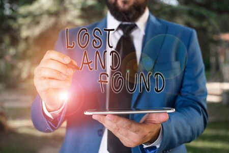 Writing note showing Lost And Found. Business concept for Place where you can find forgotten things Search service Businessman in blue suite stands with mobile phone in hands