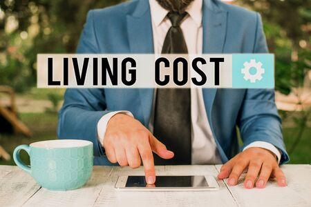 Word writing text Living Cost. Business photo showcasing the amount of money that a demonstrating needs to sustain life Businessman with pointing finger in front of him