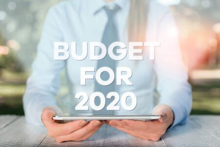 Handwriting text writing Budget For 2020. Conceptual photo An written estimates of income and expenditure for 2020 Female business person sitting by table and holding mobile phone