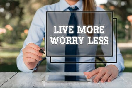 Text sign showing Live More Worry Less. Business photo showcasing Have a good attitude motivation be careless enjoy life Female business person sitting by table and holding mobile phone Stock Photo