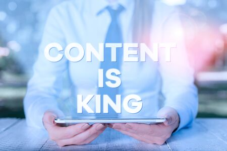 Handwriting text writing Content Is King. Conceptual photo Content is the heart of todays marketing strategies Female business person sitting by table and holding mobile phone