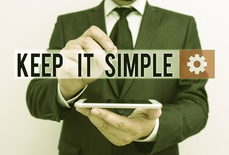 Text sign showing Keep It Simple. Business photo text Easy to toss around Understandable Generic terminology Male human wear formal work suit hold smart hi tech smartphone use one hand