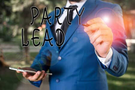 Conceptual hand writing showing Party Lead. Concept meaning acts as the official representative of their political party Businessman holds laptop and pen pointing into the copy space