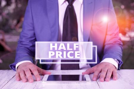 Writing note showing Half Price. Business concept for half the usual price at which something is offered for sale Businessman in blue suite with a tie holds lap top in hands