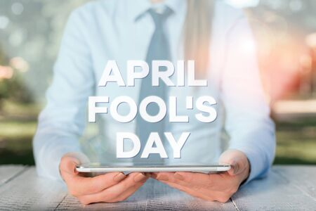 Handwriting text writing April Fools Day. Conceptual photo Practical jokes humor pranks Celebration funny foolish Female business person sitting by table and holding mobile phone Reklamní fotografie