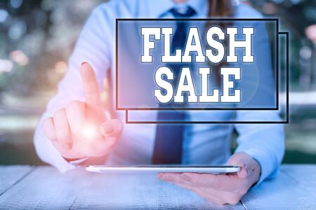 Text sign showing Flash Sale. Business photo text a sale of goods at greatly reduced prices at a short period Female business person sitting by table and holding mobile phone